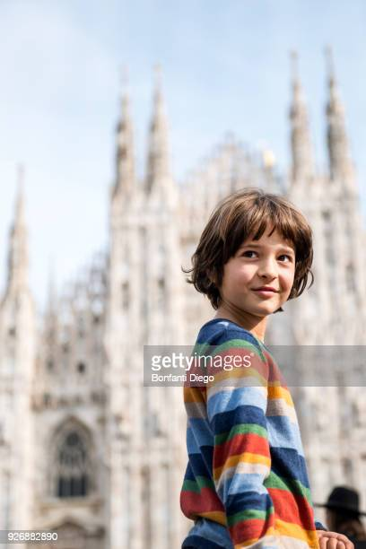 Portrait of boy looking over his shoulder in Milan Cathedral square, Milan, Lombardy, Italy