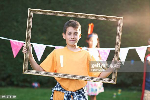 Portrait of boy looking through picture frame, looking at camera