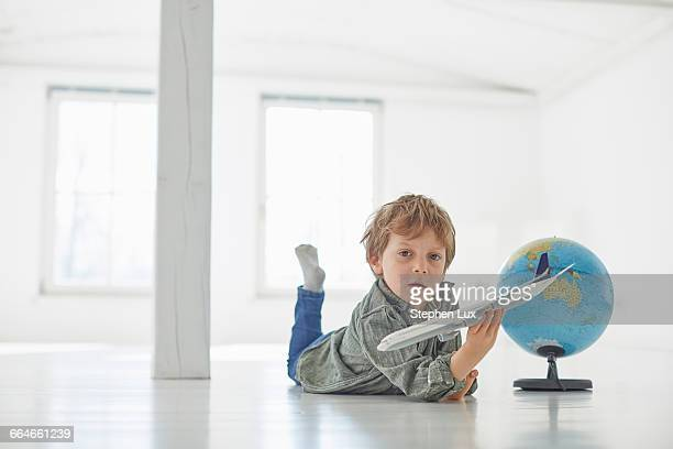 Portrait of boy lying on floor playing with globe and toy airplane