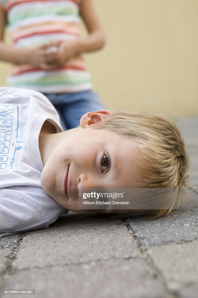 Portrait of boy (4-5) lying on ground, girl (8-9) sitting up behind : Foto stock