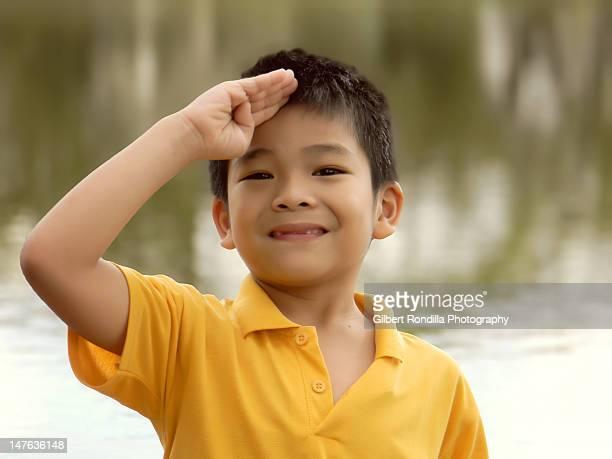 Portrait of boy making smiling salute