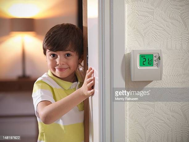 portrait of boy next to thermostat in energy efficient house - celsius ストックフォトと画像