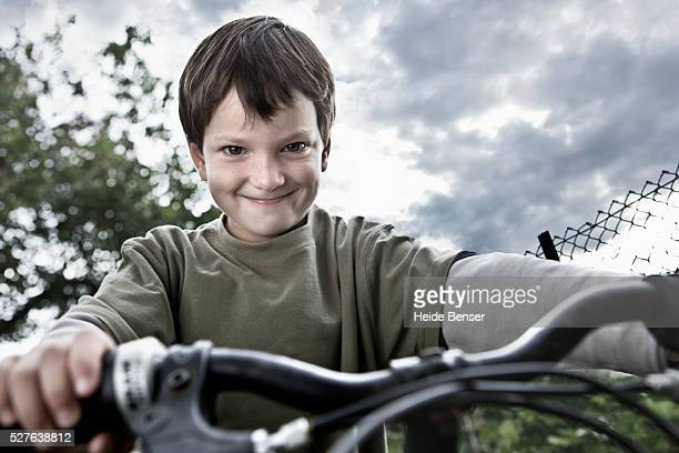portrait of boy (7-9) on bike making face - evil stock pictures, royalty-free photos & images