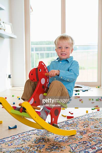 Portrait of boy playing on rocking horse
