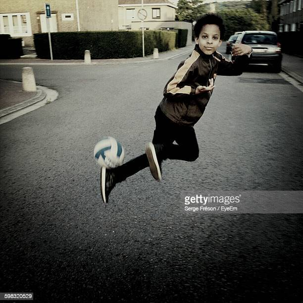 Portrait Of Boy Playing Soccer On Street In City