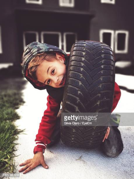 Portrait Of Boy Playing With Tire On Footpath