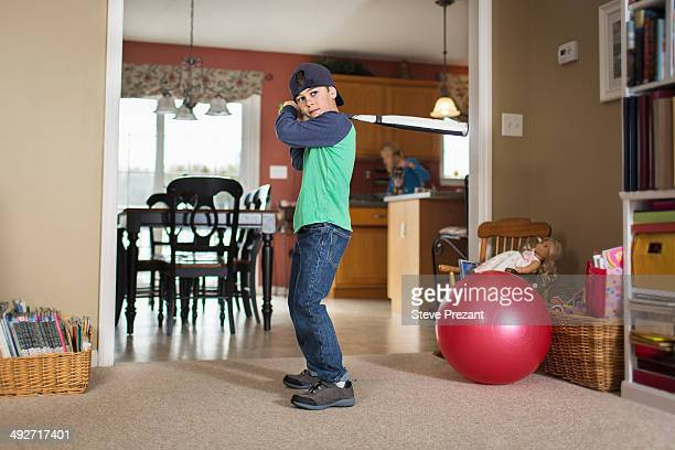 Portrait of boy practicing baseball in sitting room
