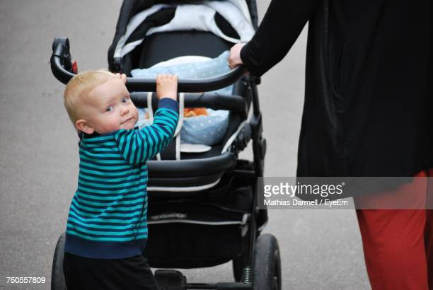Portrait Of Boy Pushing Baby Stroller With Mother On Footpath At Park