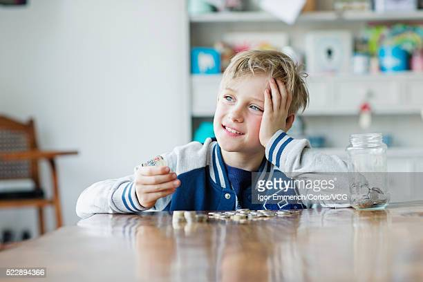 Portrait of boy ( 8-9) putting savings in glass jar
