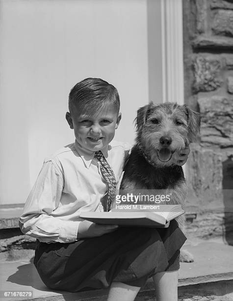 """ portrait of boy reading book, dog at side"" - pawed mammal stock pictures, royalty-free photos & images"