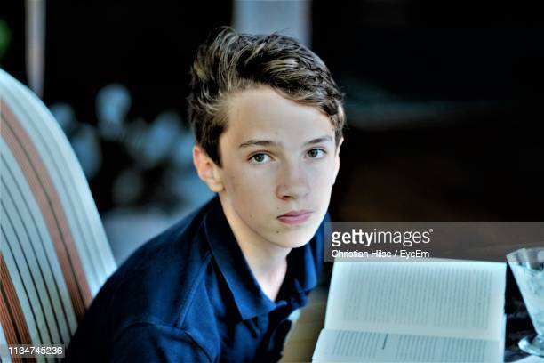 portrait of boy reading book while sitting at home - christian hilse stock-fotos und bilder