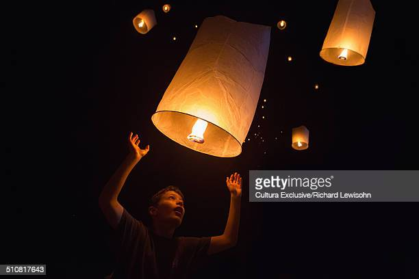 portrait of boy releasing chinese lanterns on new year's eve, krabi, thailand, southeast asia - releasing stock pictures, royalty-free photos & images