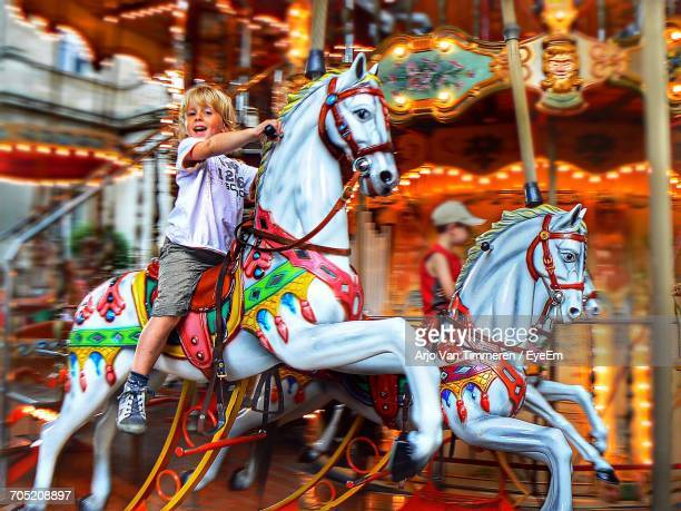 Portrait Of Boy Riding Carousel Horse
