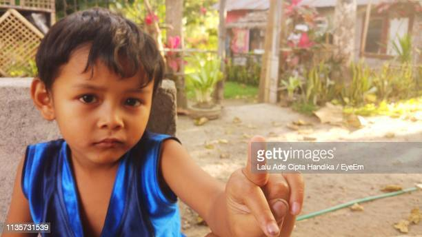 portrait of boy showing obscene gesture against plants - kid middle finger stock pictures, royalty-free photos & images