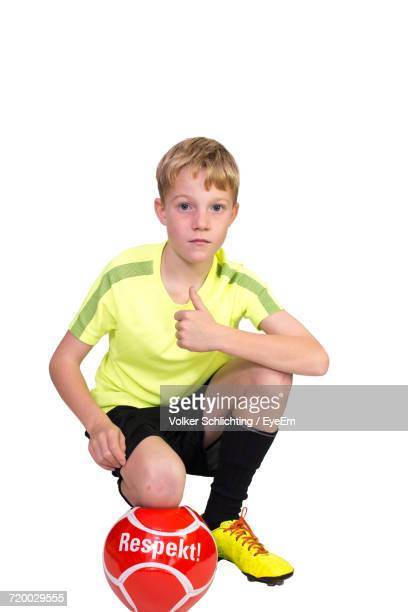Portrait Of Boy Showing Thumbs Up With Red Soccer Ball Crouching On White Background