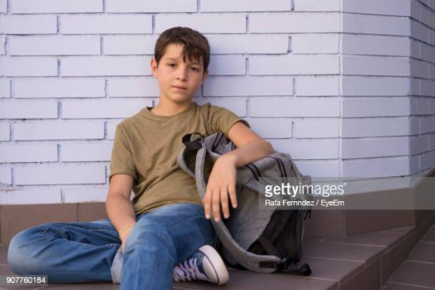 Portrait Of Boy Sitting Against Wall