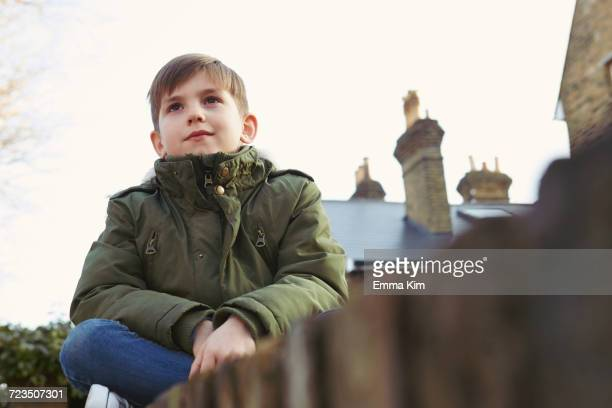 Portrait of boy sitting looking out from wall