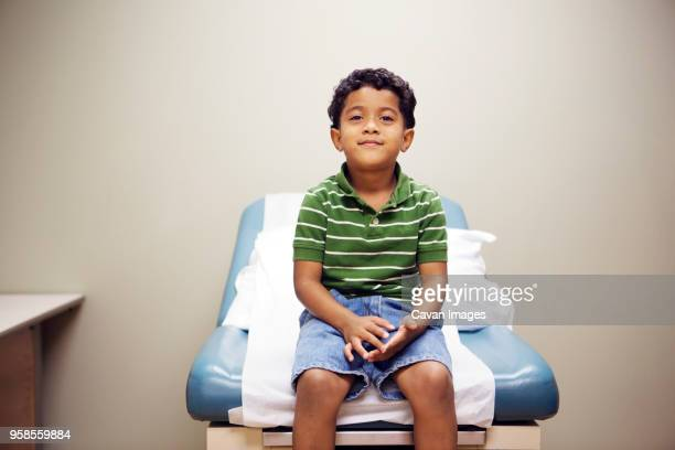 portrait of boy sitting on bed in hospital - examination table stock pictures, royalty-free photos & images