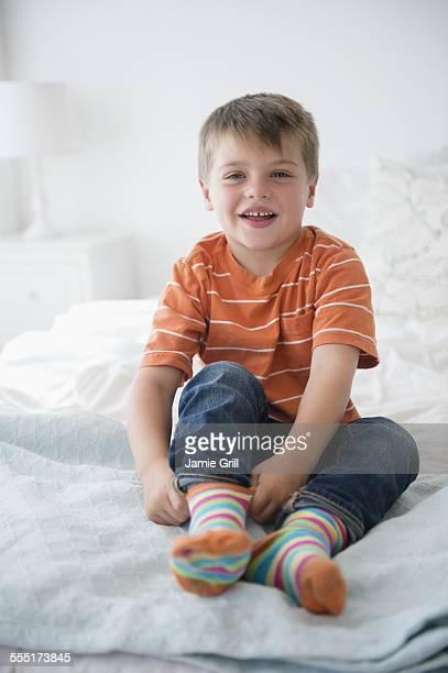 Portrait of boy (6-7) sitting on bed