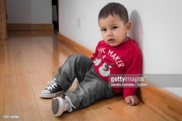 Portrait Of Boy Sitting On Floor At Home