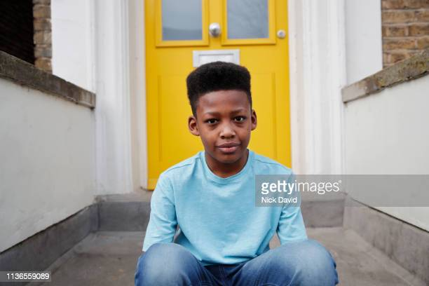 portrait of boy sitting on front doorstep - waist up stock pictures, royalty-free photos & images