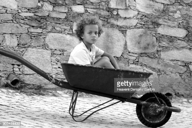Portrait Of Boy Sitting On Wheelbarrow Against Wall