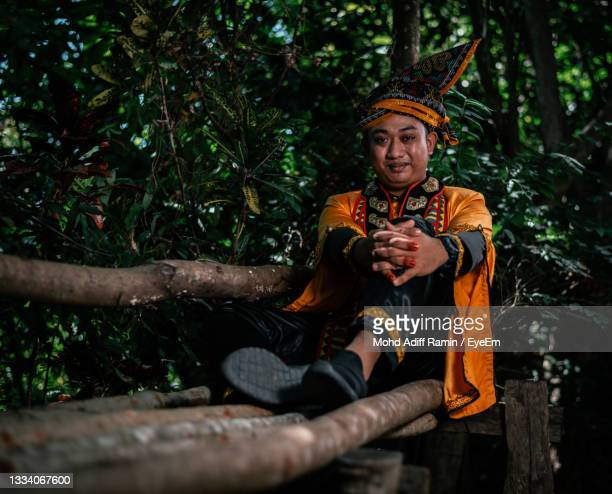 portrait of boy sitting on wood in forest,tradisonal bajau samah - bajau stock pictures, royalty-free photos & images