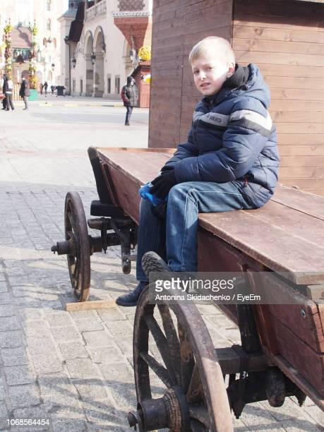 Portrait Of Boy Sitting On Wooden Cart At Footpath