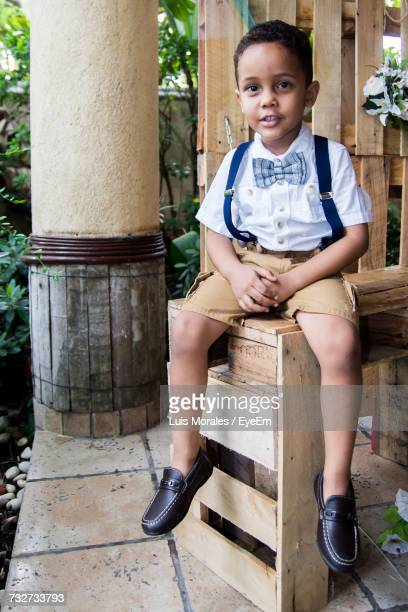 portrait of boy sitting on wooden crate - suspenders stock pictures, royalty-free photos & images