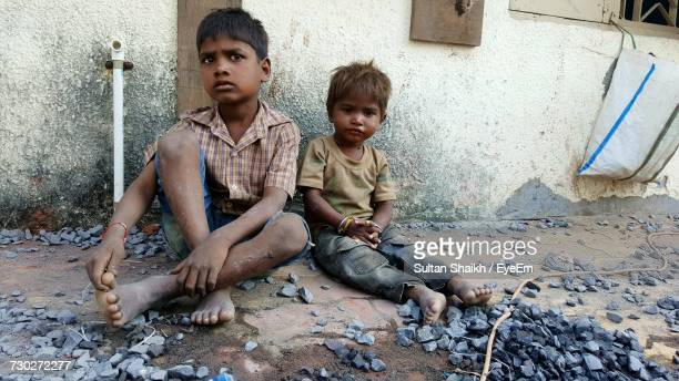 portrait of boy sitting with brother on footpath - human arm stockfoto's en -beelden