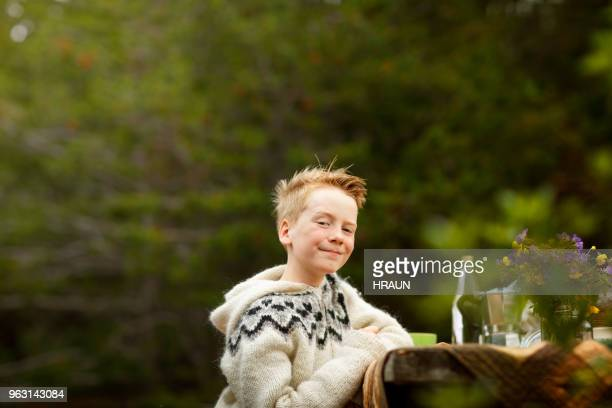Portrait of boy smiling at table in nature or yard