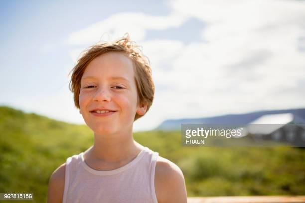 Portrait of boy smiling on patio in county side.