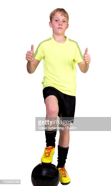 Portrait Of Boy Soccer Ball Showing Thumbs Up Against White Background