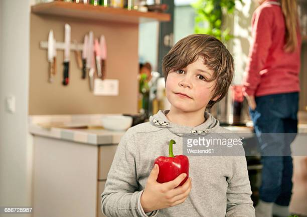 Portrait of boy standing in kitchen with red bell pepper