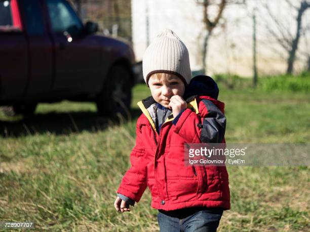 portrait of boy standing on field during sunny day - igor golovniov stock pictures, royalty-free photos & images