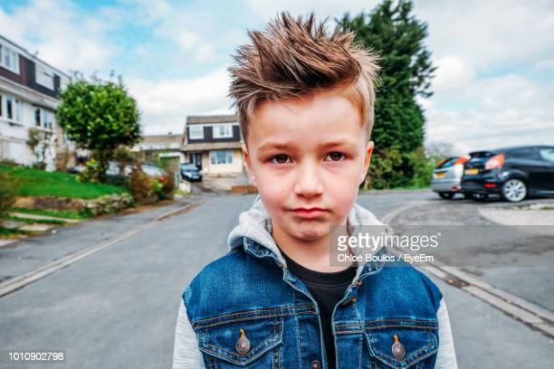 Portrait Of Boy Standing On Road Against Sky