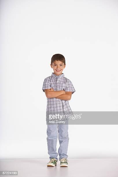 portrait of boy standing with arms crossed - jungen stock-fotos und bilder