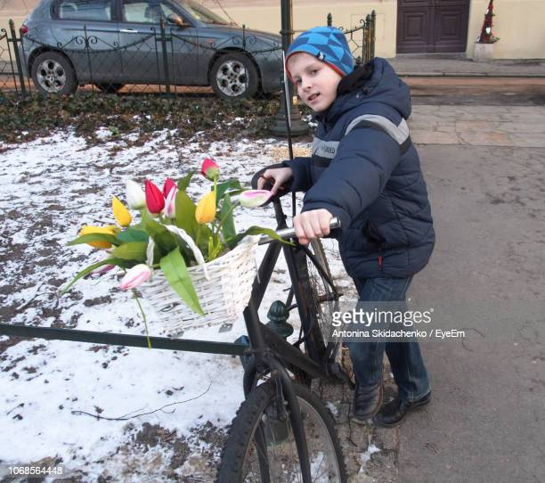 Portrait Of Boy Standing With Bicycle On Footpath During Winter
