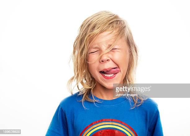 Portrait of boy sticking out tongue, studio shot
