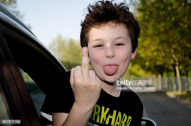 portrait of boy sticking out tongue while showing middle finger in car - kid middle finger stock pictures, royalty-free photos & images