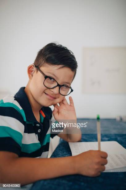 Portrait of boy studying at table in home