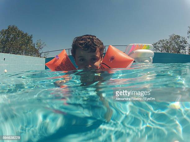 Portrait Of Boy Swimming In Pool With Water Wings