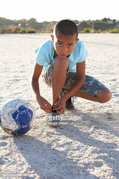 portrait of boy (10-11) tying shoelace on sand - tying shoelace stock pictures, royalty-free photos & images
