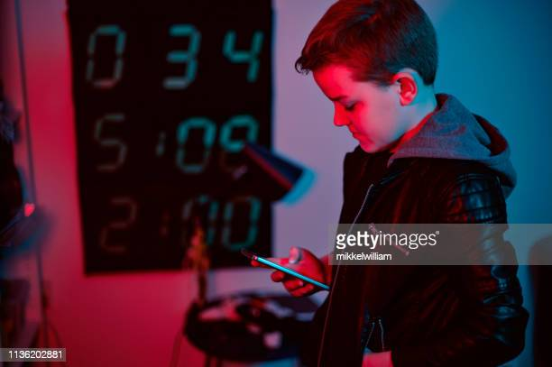 Portrait of boy typing on mobile phone and looking at the screen at night