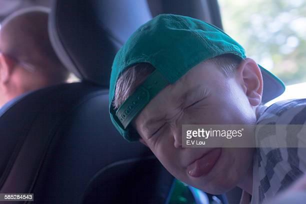 Portrait of boy wearing baseball cap pulling face in car