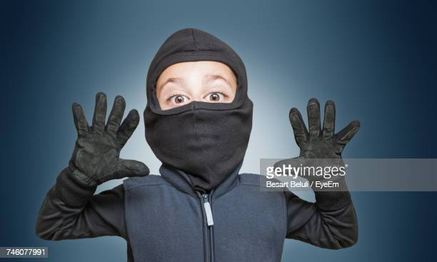 portrait of boy wearing burglar costume gesturing against blue background - stealing stock pictures, royalty-free photos & images