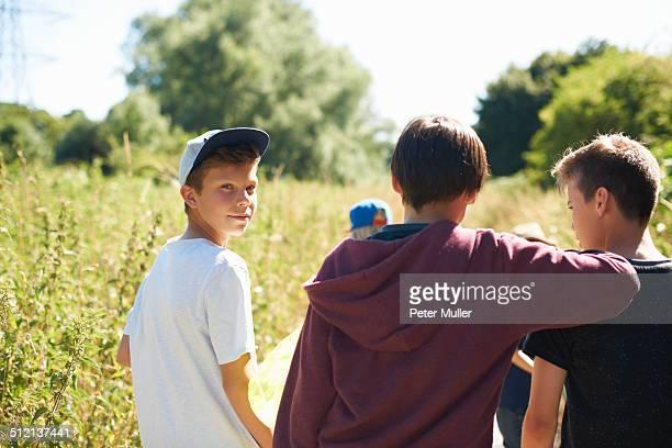 Portrait of boy wearing cap with friends