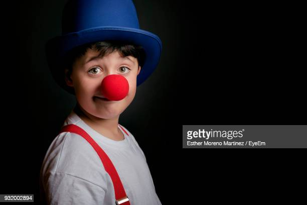 portrait of boy wearing clown costume against black background - clown's nose stock photos and pictures