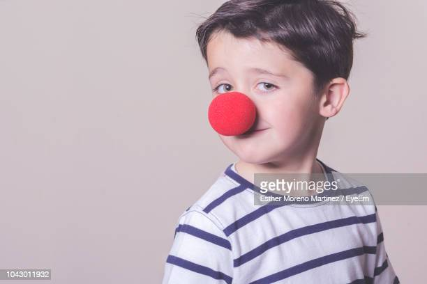 portrait of boy wearing clown nose against white background - clown's nose stock photos and pictures