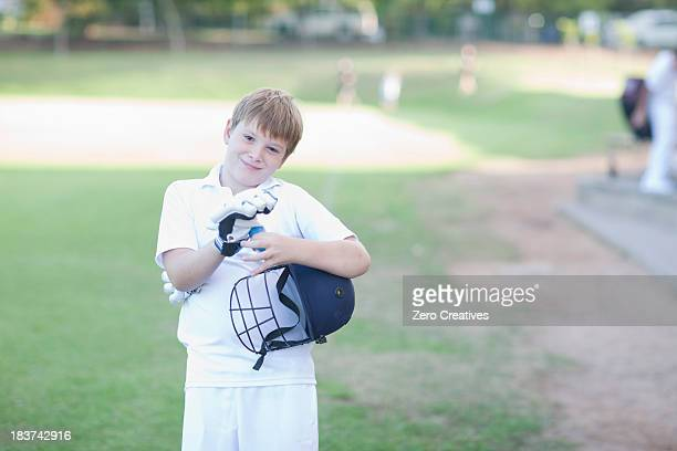 Portrait of boy wearing cricket gloves and holding helmet